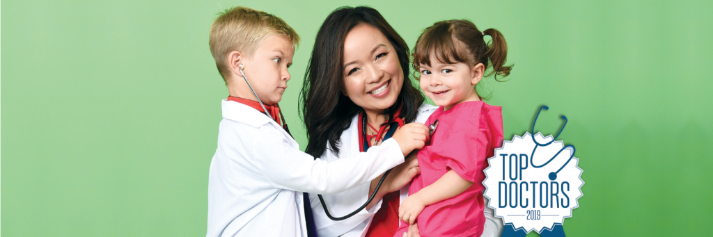 Top Doctors 2018 Banner Doctor in labcoat holding two kids, boy on left holding stethoscope to girl on right, green background