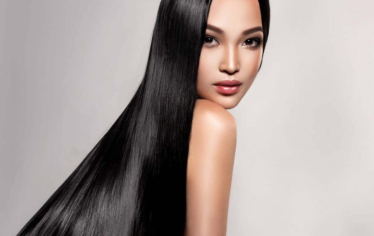 Woman with long black hair looking over her shoulder at you