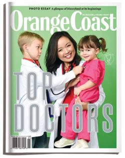 Orange Coast Top Doctors 2018 Cover Doctor in labcoat holding two kids, boy on left holding stethoscope to girl on right, green background